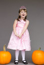 Girl kid child princess costume pumpkins halloween a is standing in a pink with for Royalty Free Stock Images