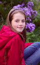 Girl kid posing near the flowers, vertical photo Royalty Free Stock Photo