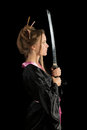 Girl in a kimono with a katana beautiful green eyed japanese hold isolated on black background Royalty Free Stock Photo