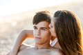 Girl kissing boy at sunset teen boyfriend on cheek Stock Photos
