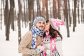 Girl kissing her boyfriend on the cheek in winter outdoors. Wearing cozy warm clothes, knitted hat and gloves . Winter dating con