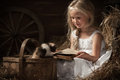 Girl with a kitten on hay reading book lying in barn Royalty Free Stock Photo