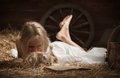 Girl with a kitten on hay reading book lying in barn Royalty Free Stock Photos