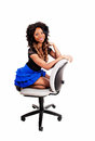 Girl kneeling on chair a lovely young jamaican woman in a blue skirt and nice black and blond long hair for isolated white Stock Photo