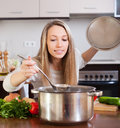 Girl with ladle cooking soup Royalty Free Stock Photo
