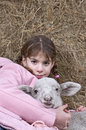 Girl with lamb in hay and lying and looking the camera Royalty Free Stock Photos