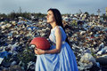 The girl in a landfill with a helmet looking to the sky