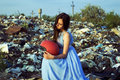 The girl in a landfill with a red helmet