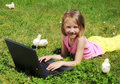 Girl with laptop  laying on green grass Stock Photo