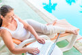 Girl with a laptop in a lounge chair Royalty Free Stock Photo