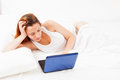 Girl with laptop lying in her bed at home Royalty Free Stock Photo