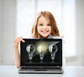 Girl with laptop pc at school education technology and internet concept little student pointing light bulbs Royalty Free Stock Photos