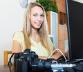 Girl with laptop and photocamera smiling working Stock Image