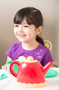 Girl laughing as she plays tea party happy toddler smiles and laughs has a Stock Photography