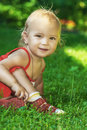 Girl laughs the small beautiful sits on a green lawn and Stock Photo