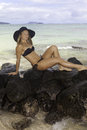 Girl on lava rocks by the ocean in bikini and hat lounging Stock Images
