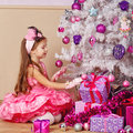 Girl lays out the gifts under Christmas tree. Royalty Free Stock Photo