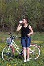 The girl leans on a parked bike. Rest on the spring cycle. The girl drinks water from a bottle Royalty Free Stock Photo