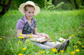 Girl learning in meadow with hat reading book dandelions Royalty Free Stock Photography