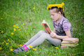 Girl learning in meadow reading book dandelions Royalty Free Stock Photography
