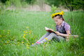 Girl learning in meadow reading book dandelions Royalty Free Stock Images
