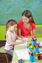 Girl learning to write in preschool class with nursery teacher Stock Photos