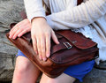 Girl with leather handbag brown sitting on wooden bench and holding bag in her lap Stock Photography