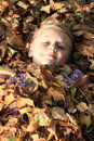 Girl in leaves little lila pullover covered by dead brown Royalty Free Stock Photo