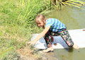 Girl leaving surf barefoot hairy kid in wet clothes board in water of pond Stock Photo