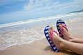 Girl legs in colorful flipflop on beach Royalty Free Stock Photos