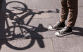 Girl legs wearing black snickers and skinny brown trousers in front of the shadow of a bicycle Royalty Free Stock Photo