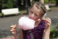 Girl licks cotton candy in the park Stock Image