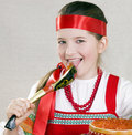 Girl  licks a spoon with red caviar Royalty Free Stock Photos
