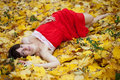 Girl lies in maple leaves Stock Photos