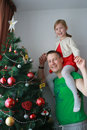 Girl lift in the fathers shoulders next to the Christmas tree Royalty Free Stock Photo