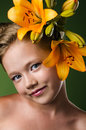 Girl with lily flowers in hair over green background Royalty Free Stock Image