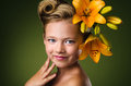 Girl with lily flowers in hair over green background Stock Photo
