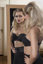 Girl in lingerie in front of the mirror cool blonde woman with black bra and glamour style posing fashion shoot Stock Photography