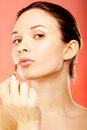 Girl with lipgloss portrait of young gorgeous female applying Royalty Free Stock Image