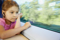 Girl listens to music, sitting by window of train Stock Images