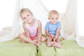 Girl with little brother happy kids sister and relaxing on a bed over white Stock Images