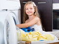 Girl loading linen to washing machine Royalty Free Stock Photo