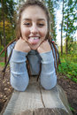 Girl on log young woman with dreadlocks lays in wood and tongue out Stock Image