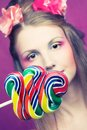 Girl with lollipop portrait of young woman and pink flowers in her hair Stock Photos