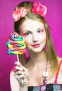 Girl with lollipop portrait of young woman and pink flowers in her hair Royalty Free Stock Photos