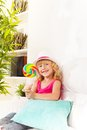 Girl with lollypop at home little sitting on coach in living room hat Royalty Free Stock Image
