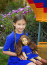 A girl with long brown braided hair and brown eyes plays with her look a like american girl doll both wearing the same blue dress Stock Image