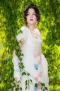 Girl in a long, elegant white bride dress in a park.