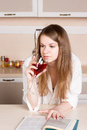 Girl with long flowing hair  man's shirt in the kitchen  glass of red wine Royalty Free Stock Photo
