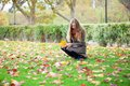 Girl with long hair gathering autumn leaves Royalty Free Stock Image
